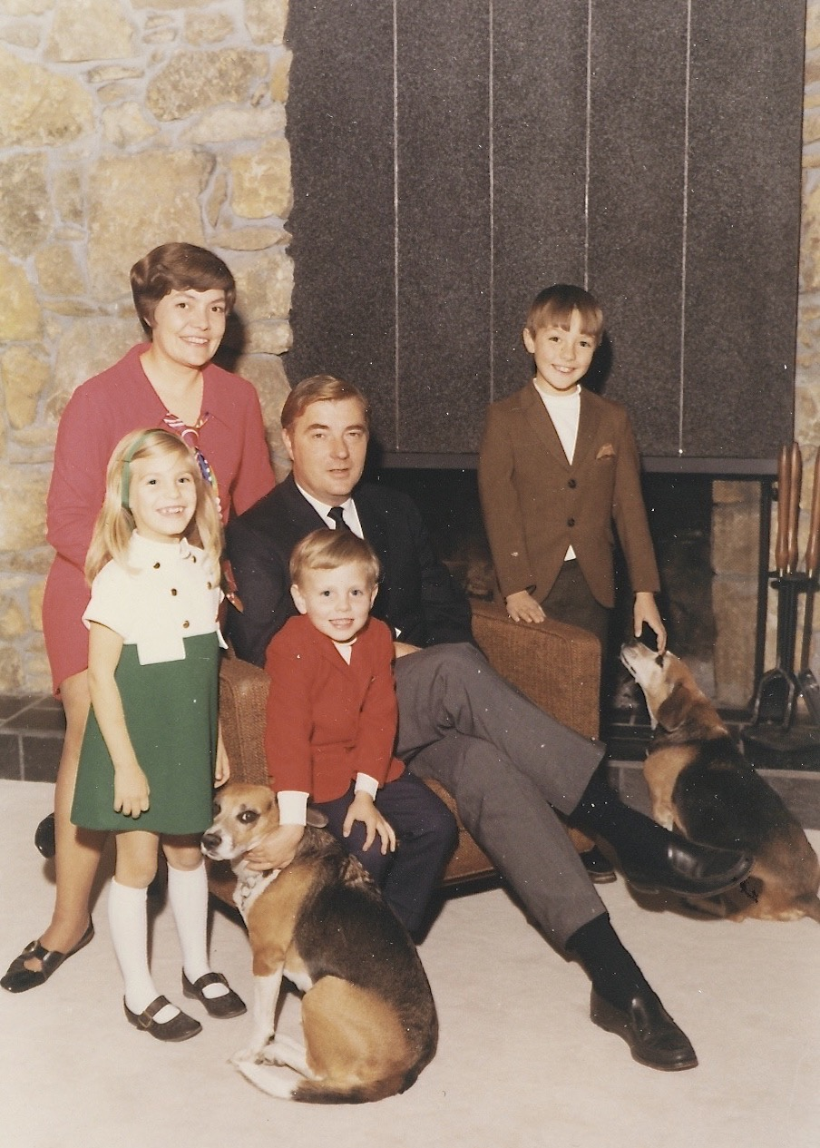 Laura, Mom and Dad, John, and me (with beagles and my bangs), circa 1968.